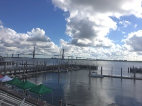 View of the Ravenel Bridge across the water underneath a cloudy sky.